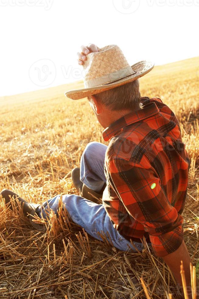 älterer Bauer, der auf Feld sitzt foto