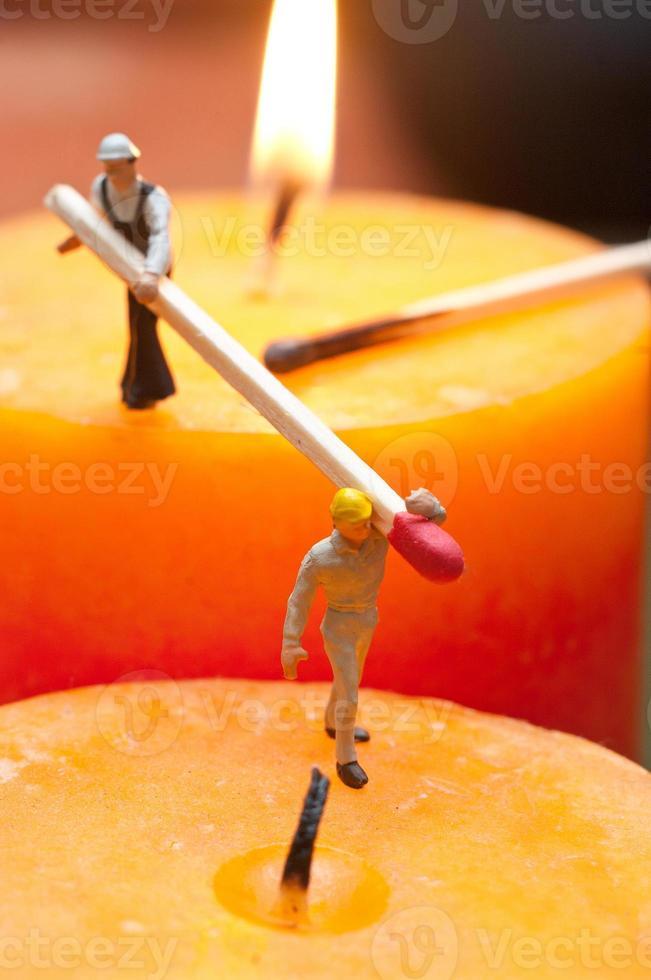 Zwei kleine Arbeiter zündeten Kerzen an. das Konzept der Teamarbeit foto