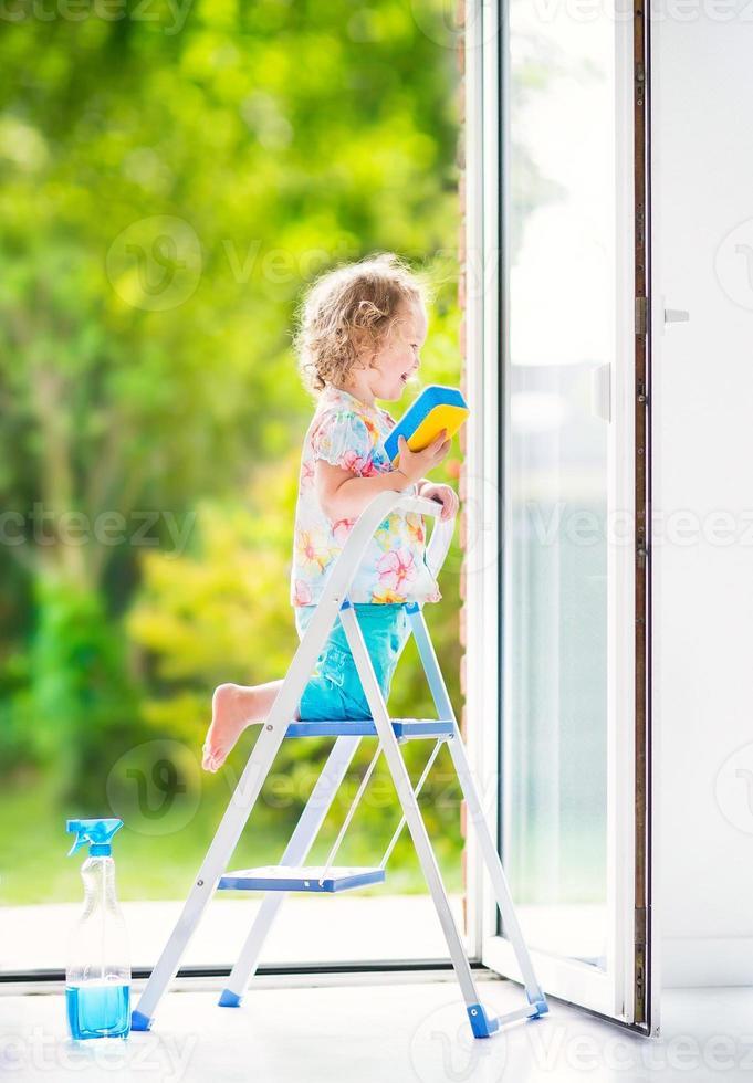 hübsches Kleinkindmädchen, das ein Fenster wäscht foto