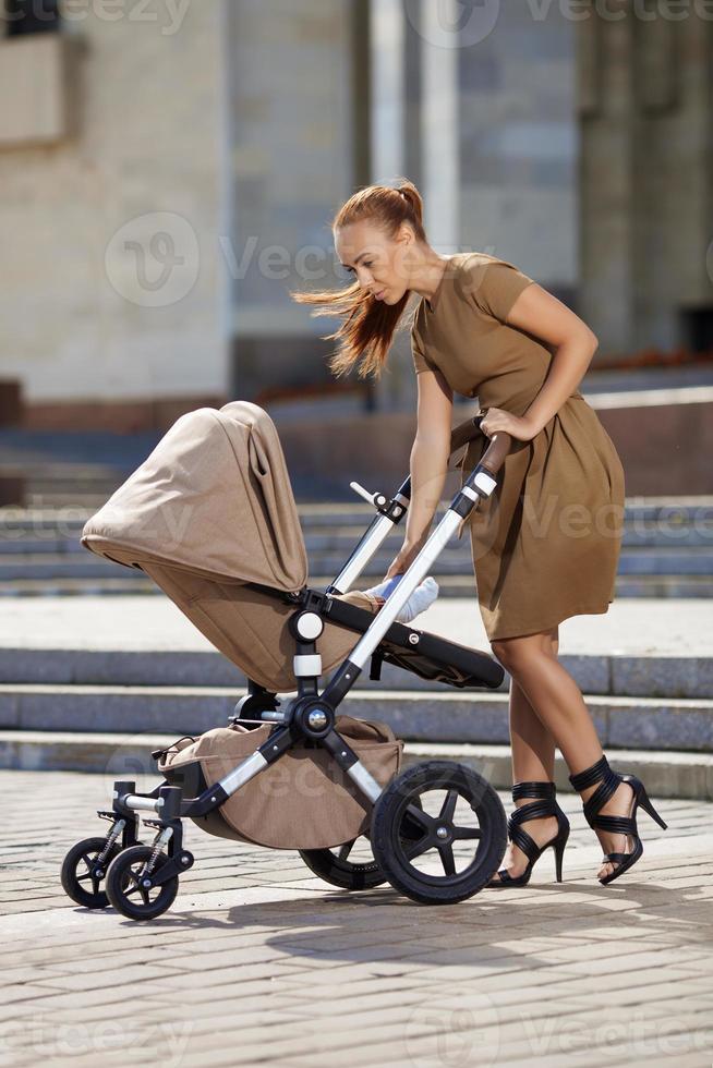 modische moderne Mutter auf einer städtischen Straße mit einem Kinderwagen. foto