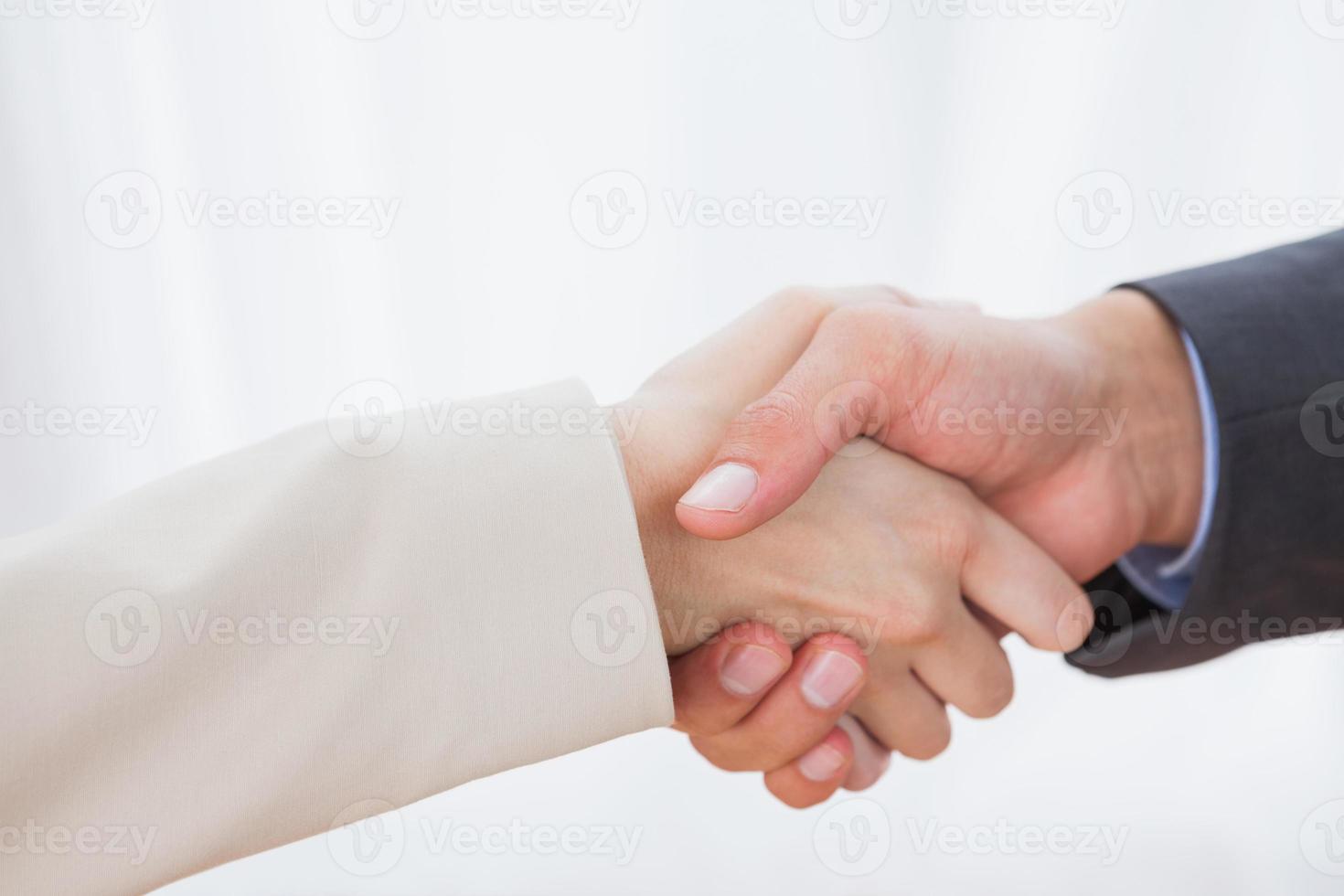 Nahaufnahme von Partnern, die sich die Hände schütteln foto