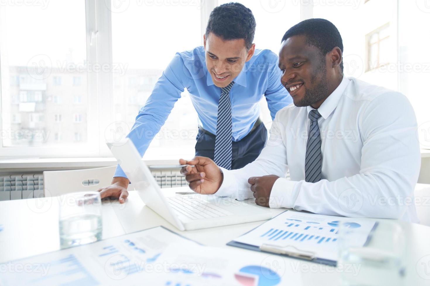 zwei Geschäftsleute, die an einem Laptop in einem Konferenzraum arbeiten foto