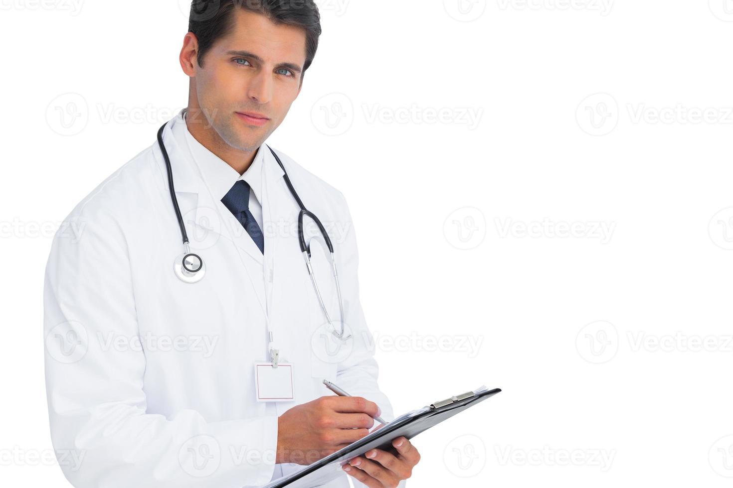 Doktor schreibt in seine Zwischenablage und schaut in die Kamera foto