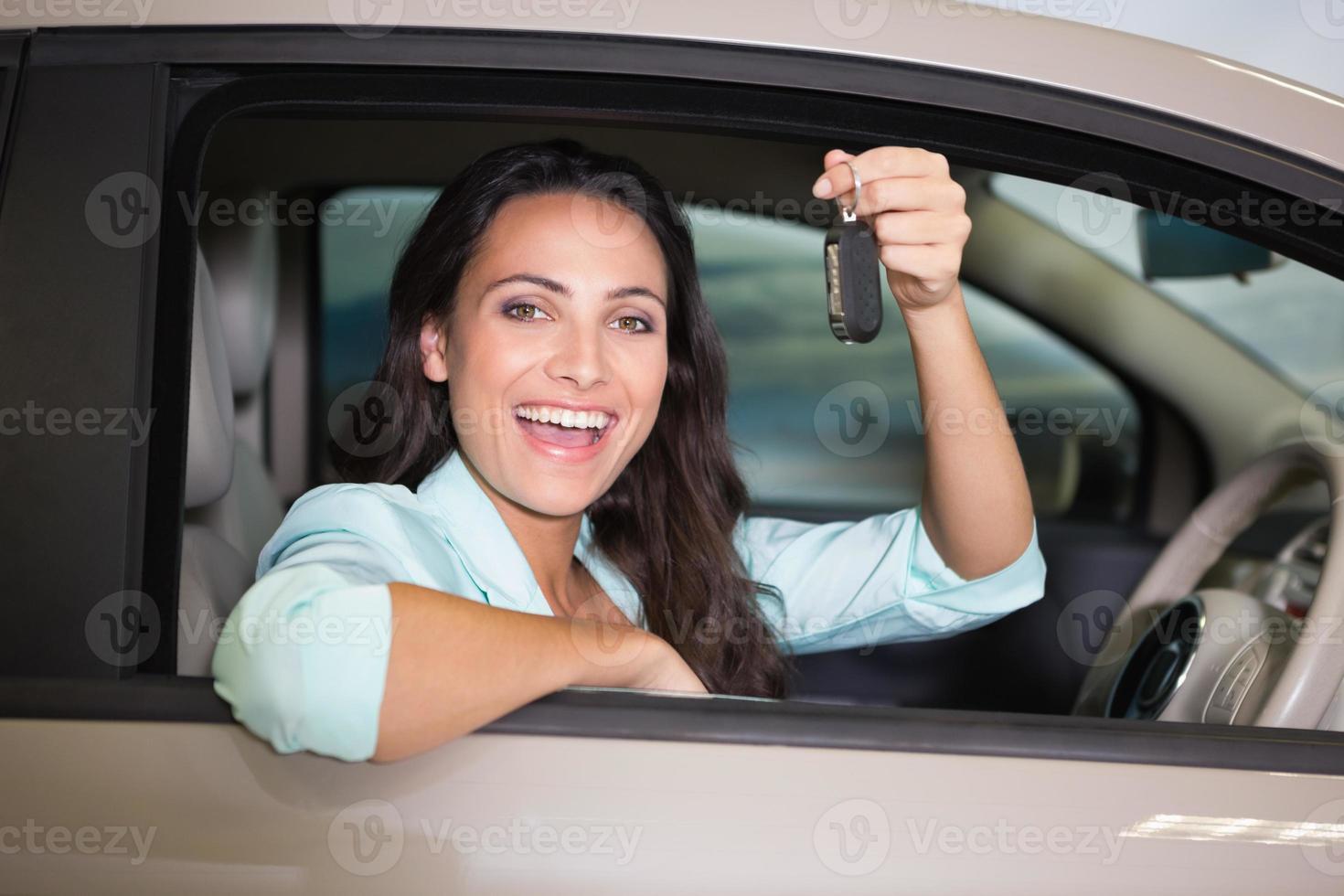 lächelnde Frau, die Autoschlüssel hält foto