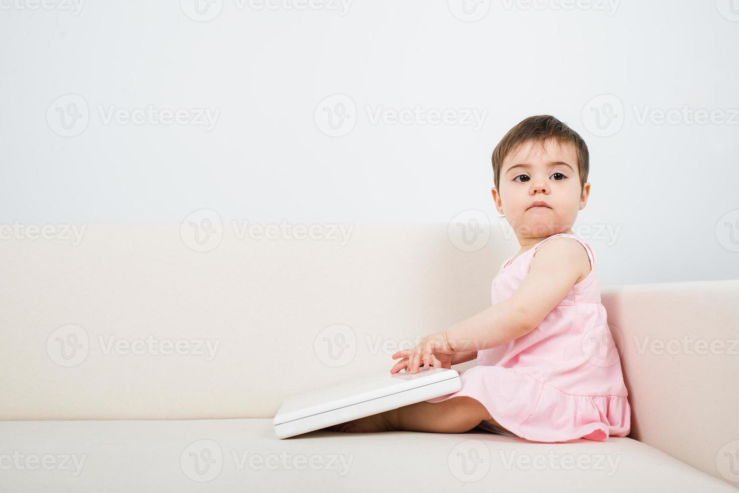 junges Baby sitzen und mit einem Laptop wegsehen foto