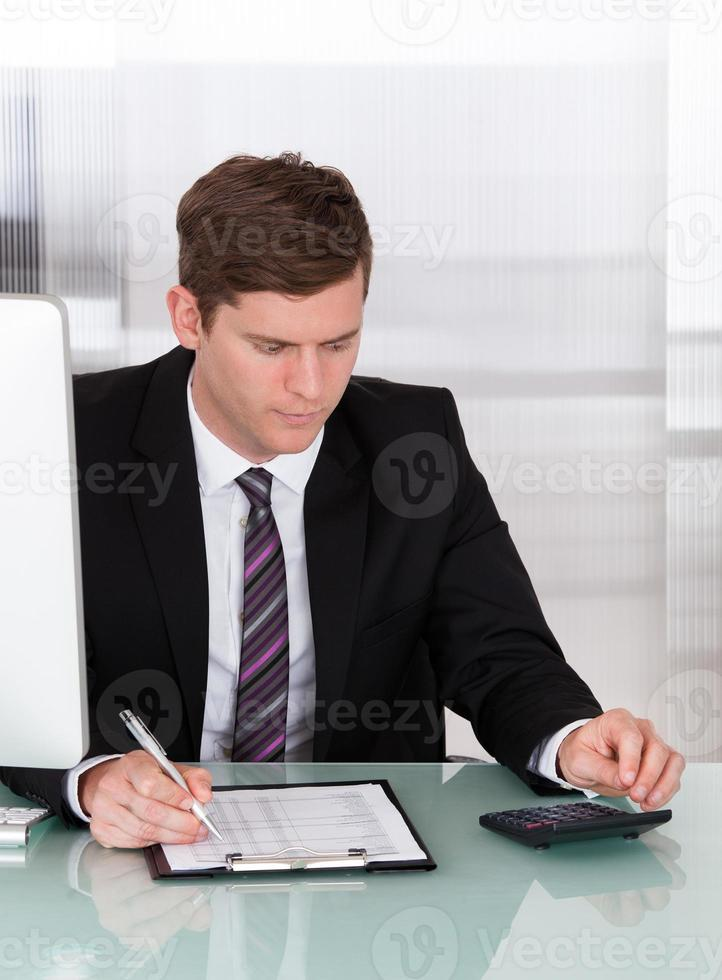junger Mann, der Finanzen berechnet foto