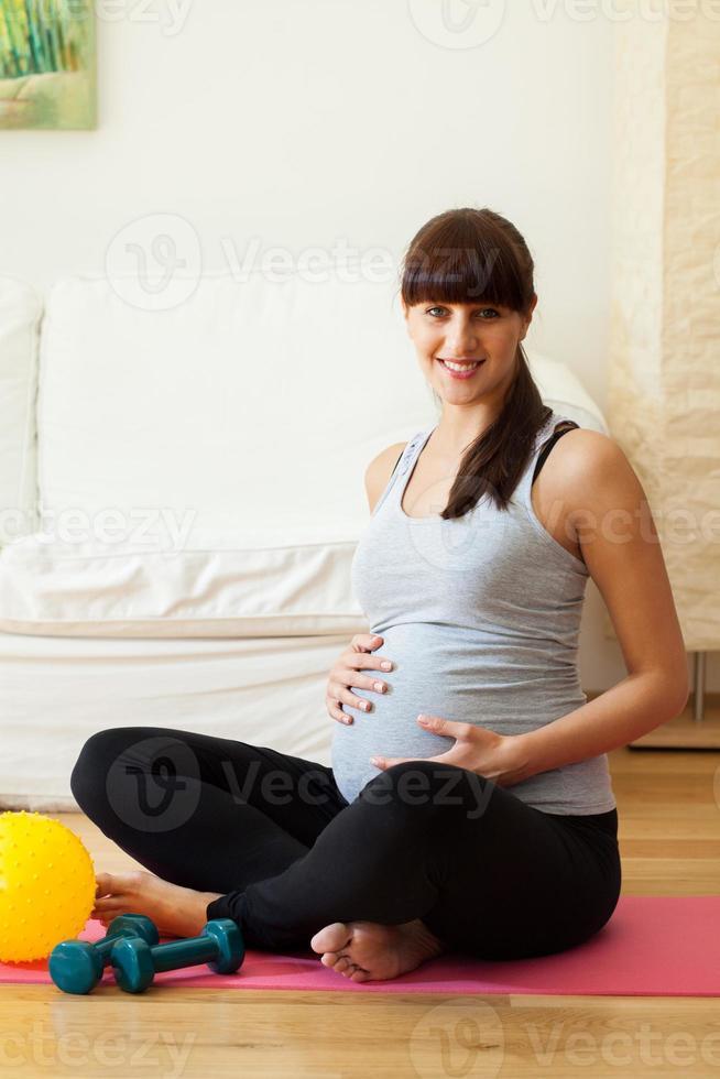 gravide Frau, die Pause von den Fitnessübungen macht foto