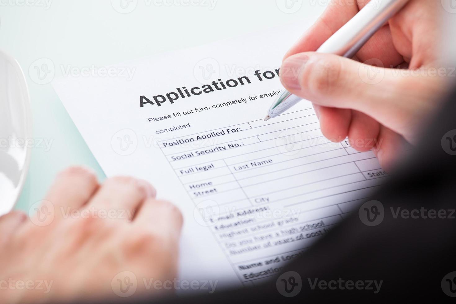 Person, die ein Formular von Hand ausfüllt foto
