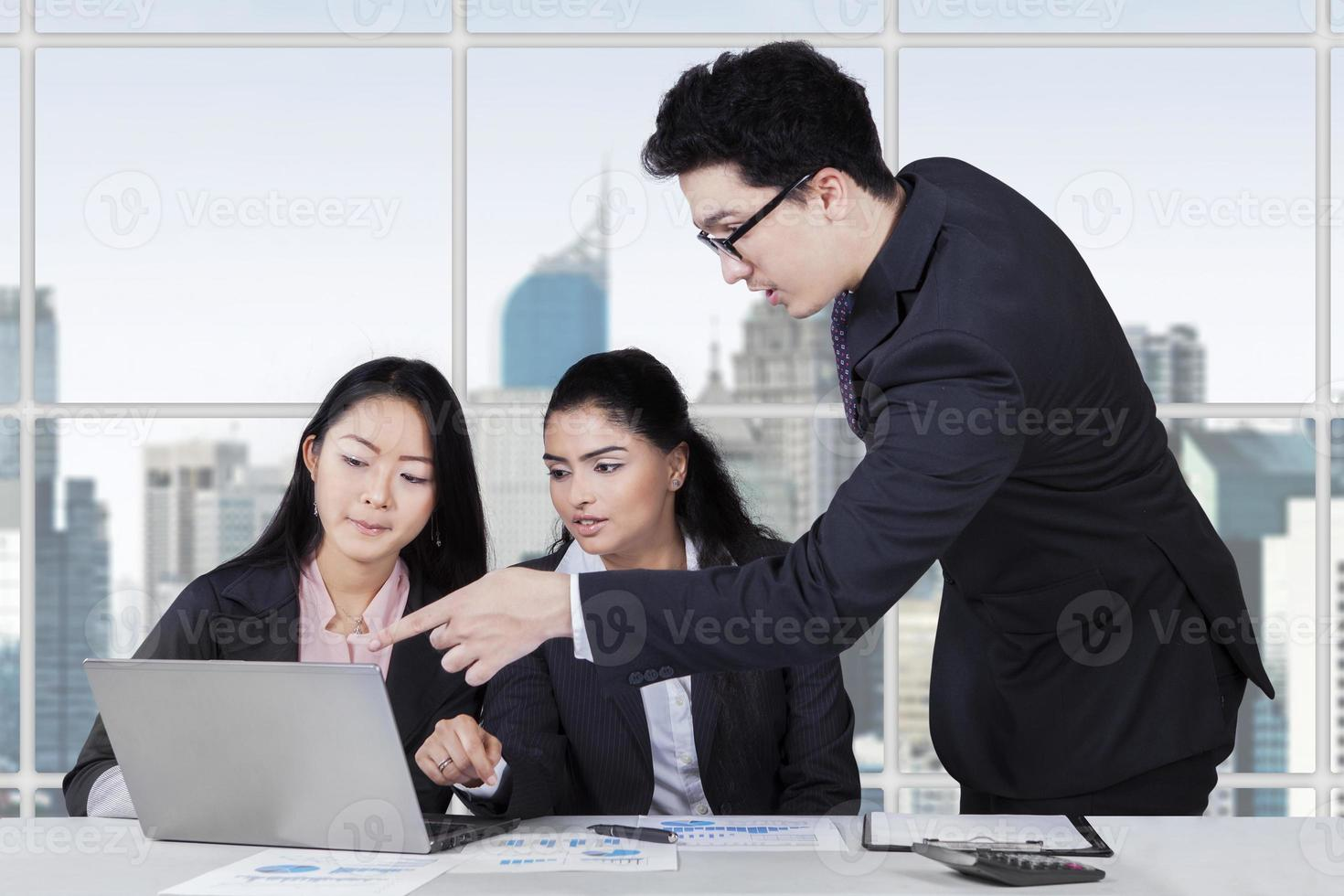 männlicher Trainer, der einen Job im Büro erklärt foto