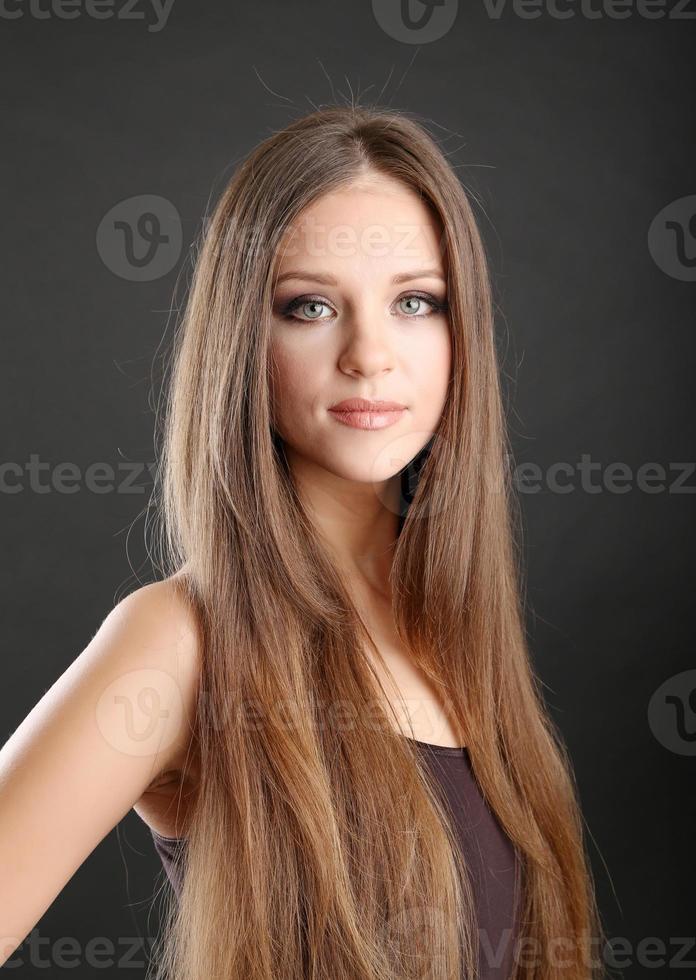 Porträt der schönen Frau mit langen Haaren auf schwarzem Hintergrund foto