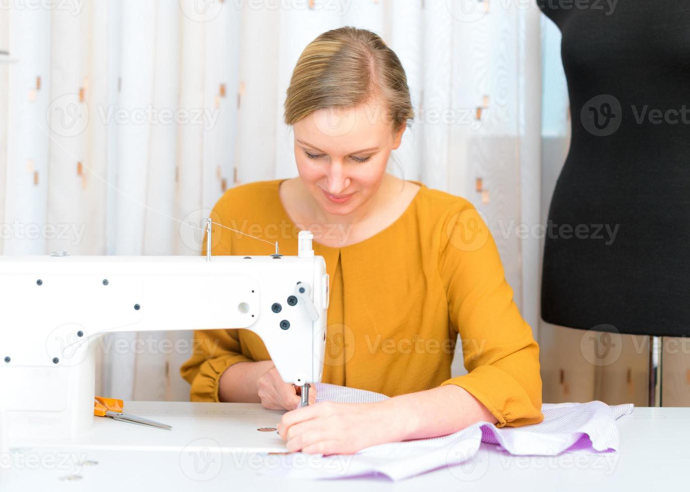 Frau arbeitet an Nähmaschine in der Fabrik. foto