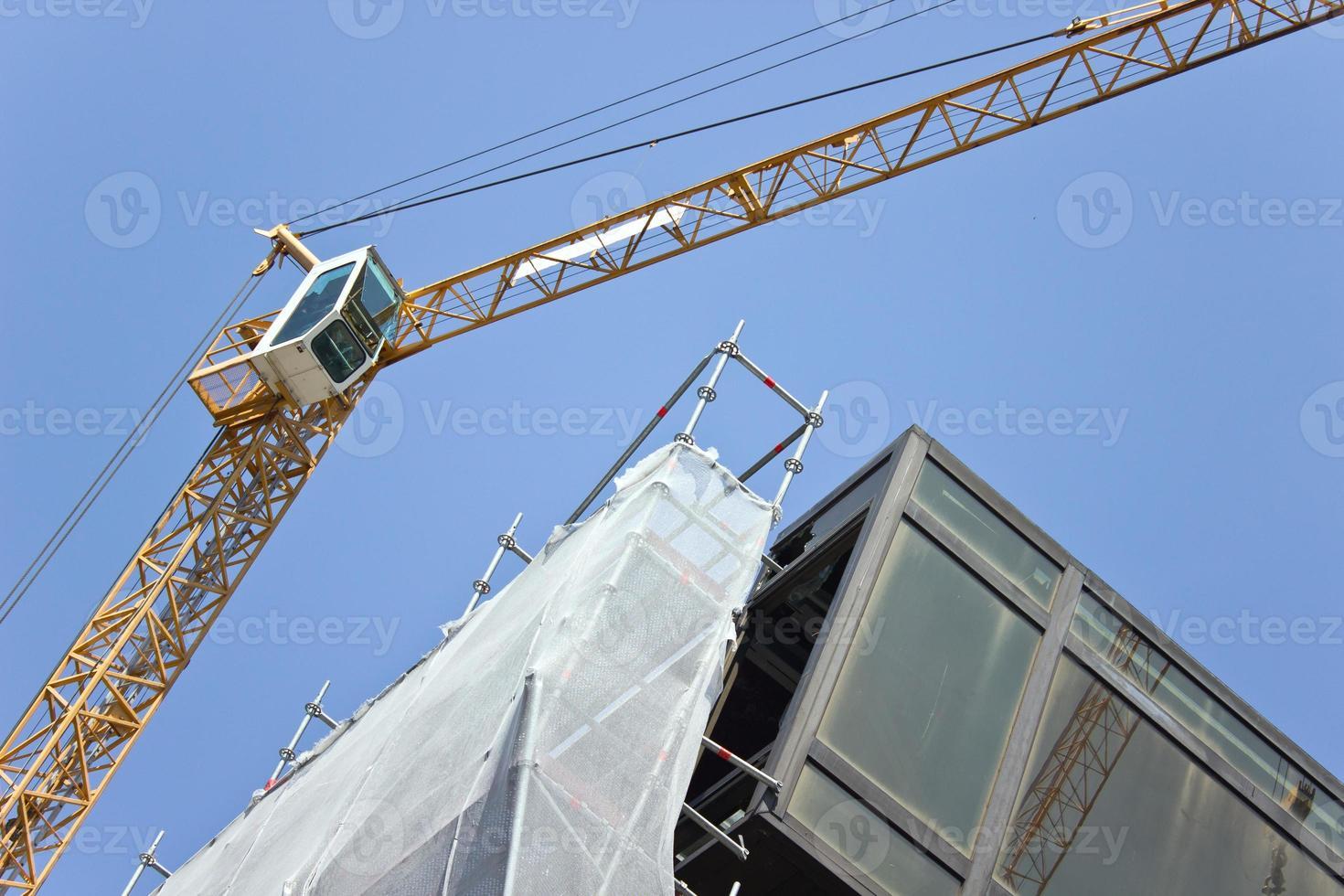Baustelle mit Kränen gegen blauen Himmel foto