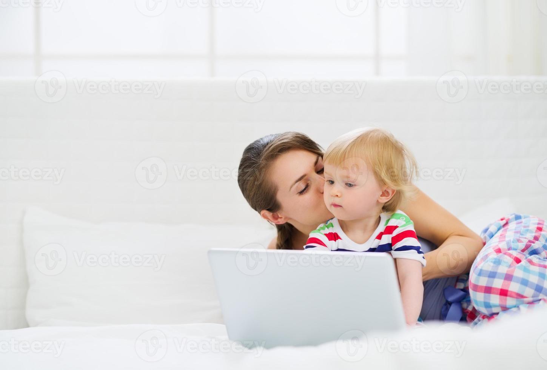 junge Mutter küsst ihr modernes Baby, das am Laptop arbeitet foto