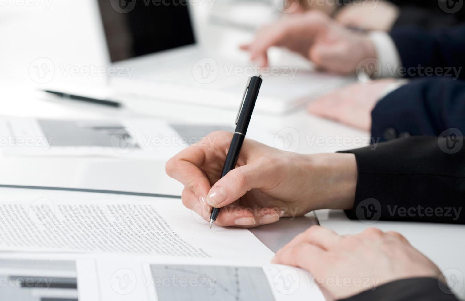 Hände der Geschäftsfrau, die Notizen mit einem Stift machen foto