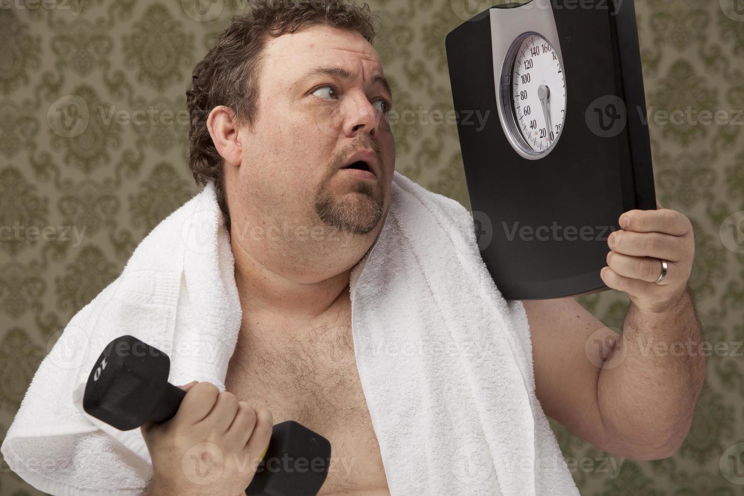 Übergewichtige männliche Haltewaagen arbeiten hart, um Gewicht zu verlieren foto