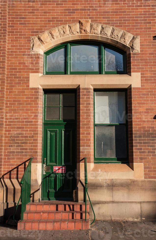 rote Backsteinmauer mit grüner Tür und Fenster foto
