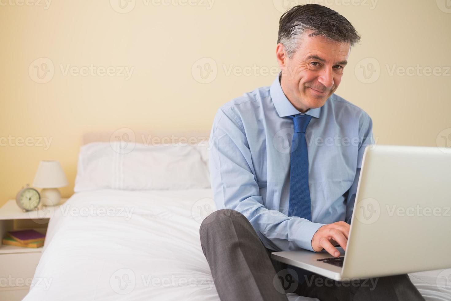 zufriedener Mann, der seinen Laptop benutzt, der auf einem Bett sitzt foto