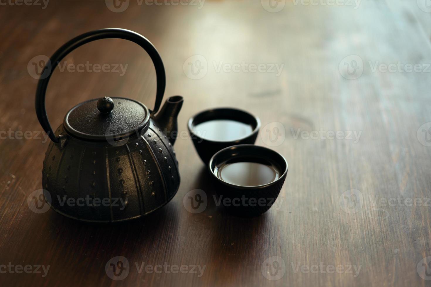 Bild der traditionellen östlichen Teekanne und der Teetassen auf Holzschreibtisch foto