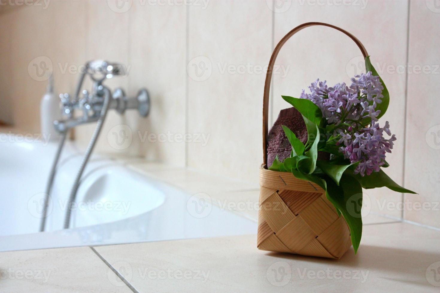 Korb mit Handtuch und Blumen im Badezimmer foto
