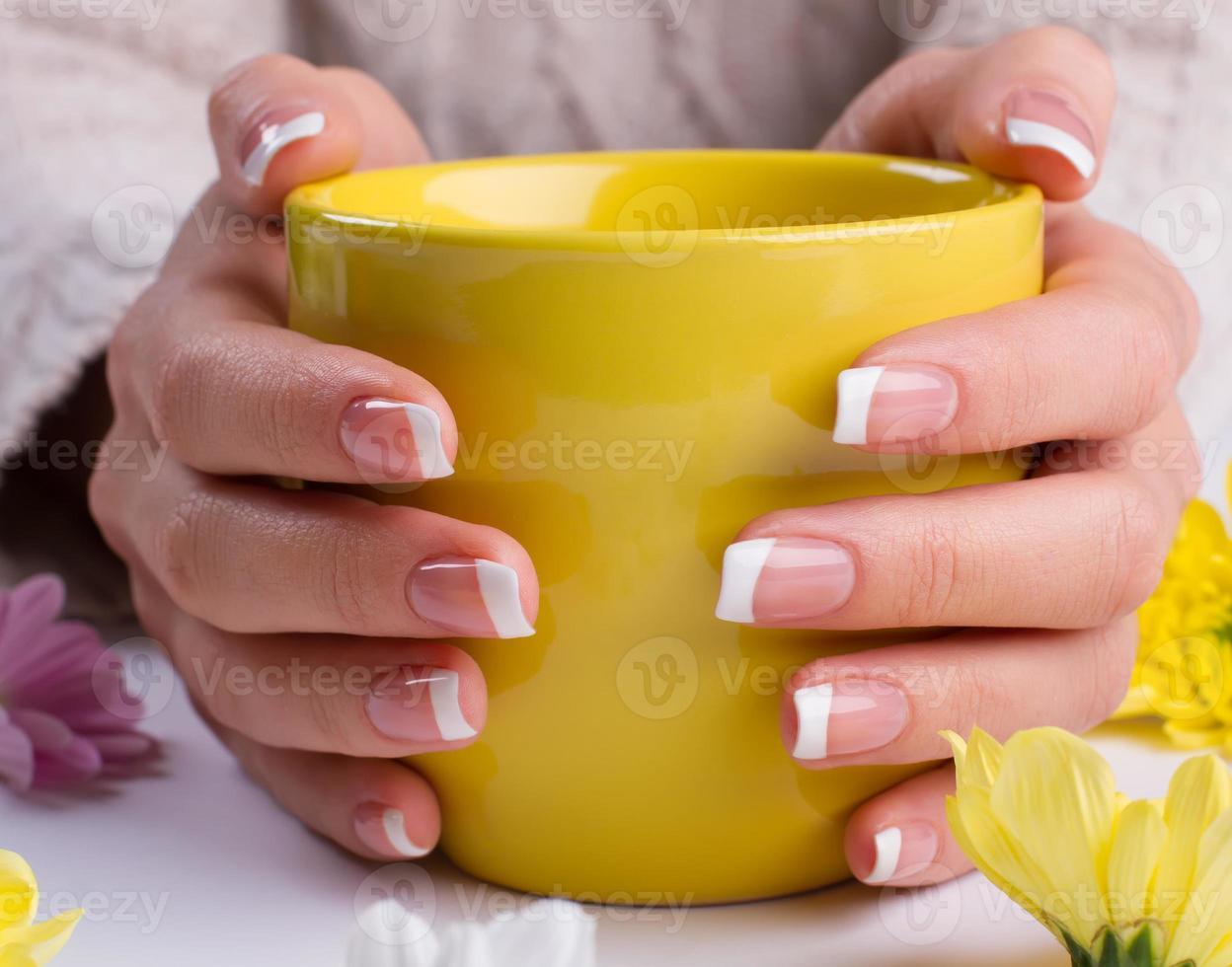 Frau hält eine gelbe Tasse in der Nähe. foto