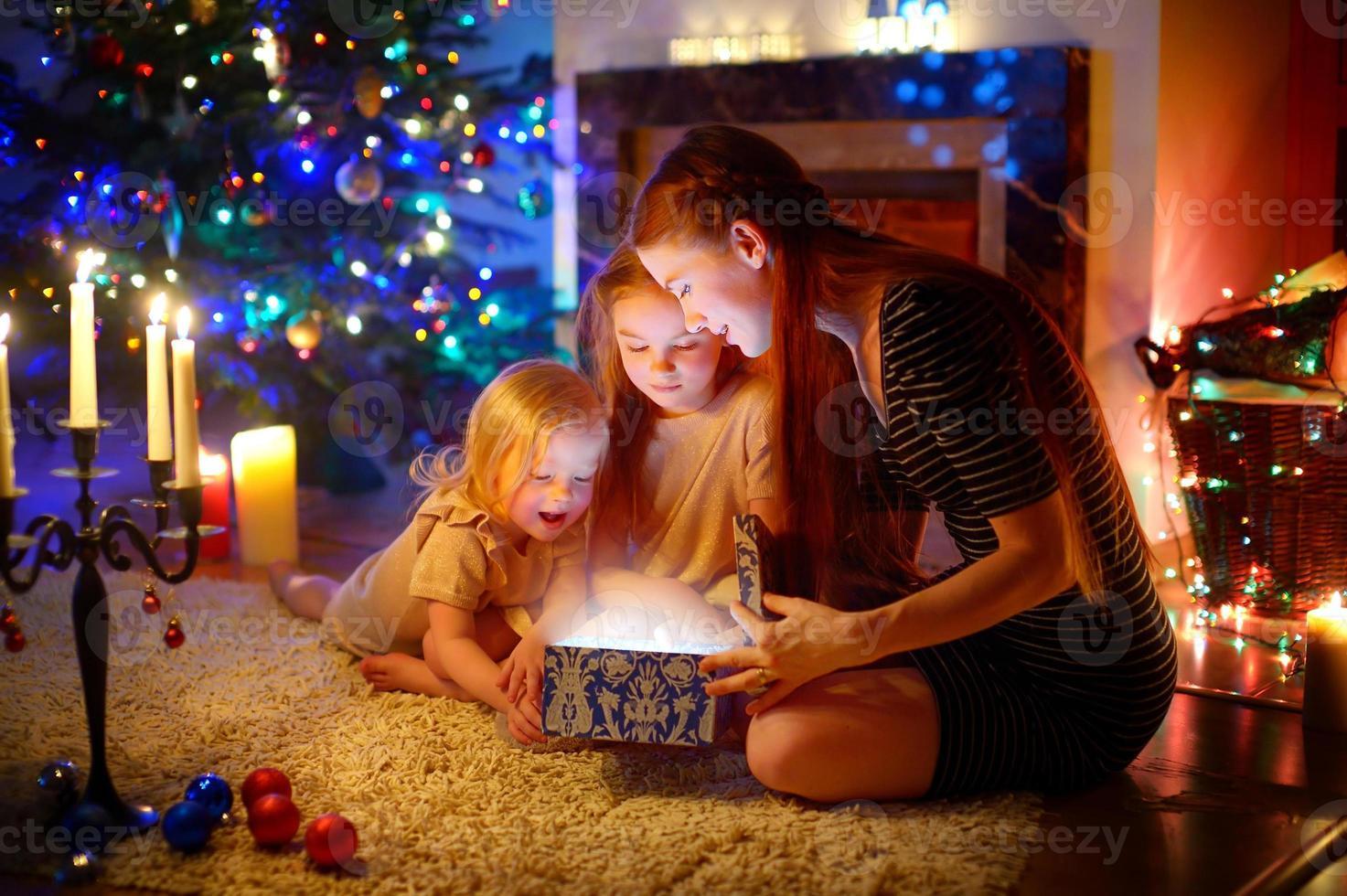 Mutter und zwei kleine Töchter eröffnen ein magisches Weihnachtsgeschenk foto