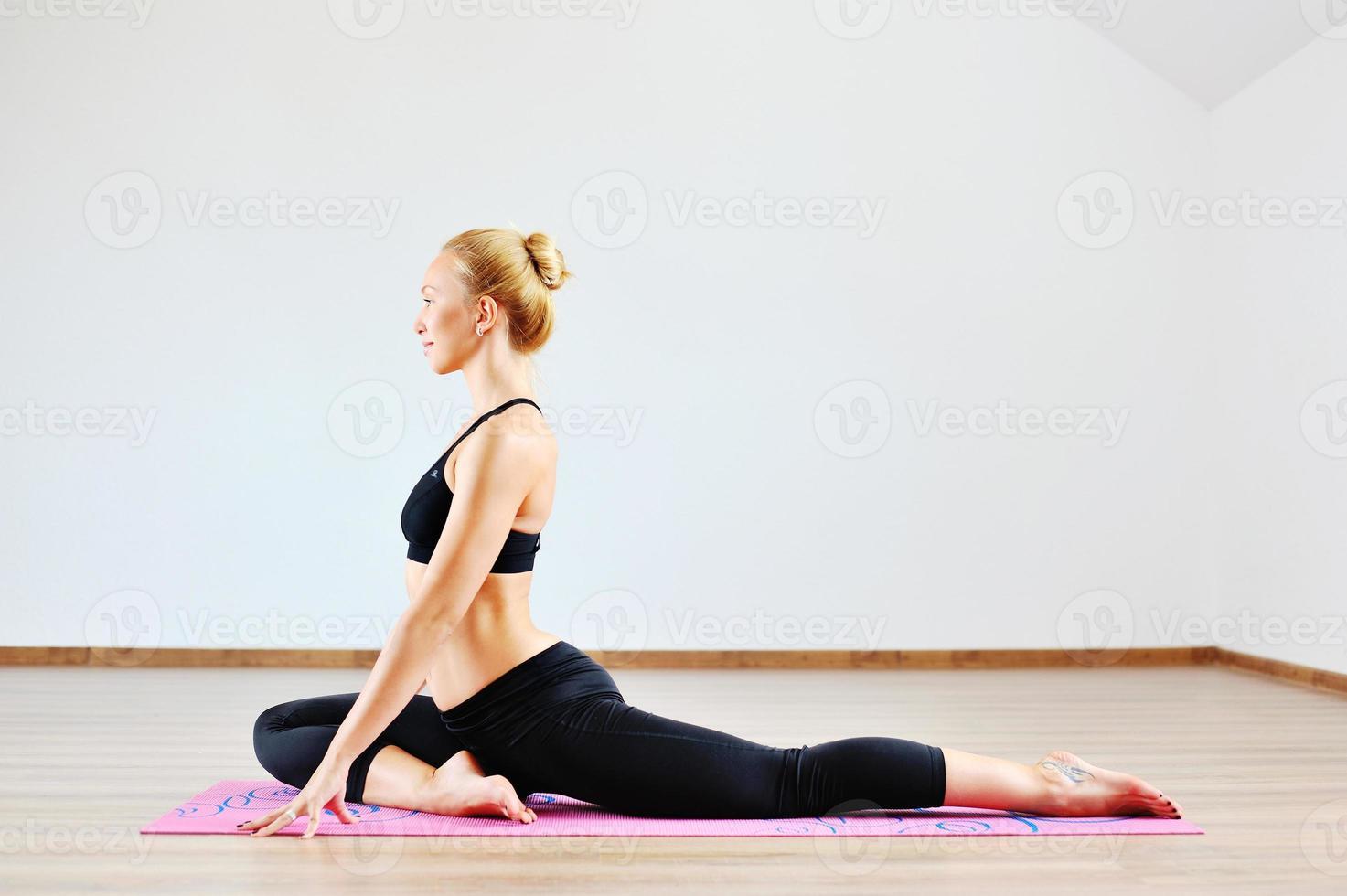 schöne kaukasische Frau, die Yoga drinnen ausübt foto