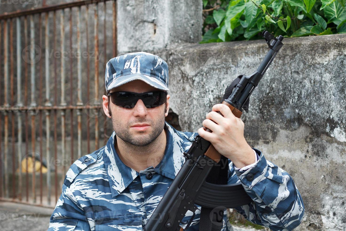 Porträt des militärischen kaukasischen Mannes in der städtischen Kriegsführung, die Gewehr hält foto