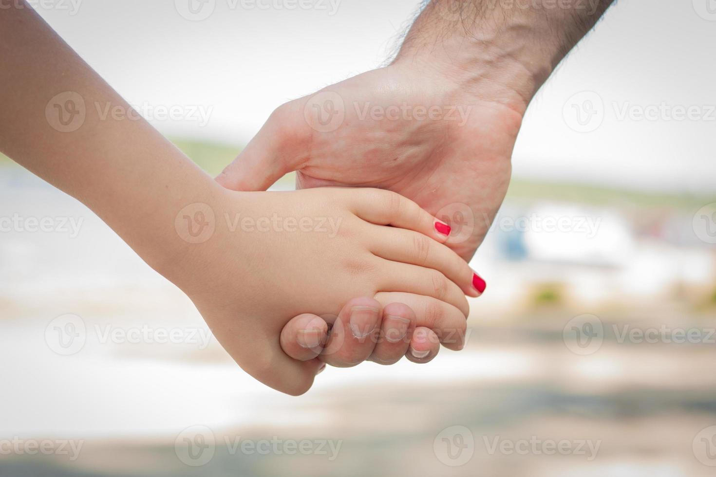 Hand des kaukasischen Mannes, die die Hand eines Kindes an einem See hält foto