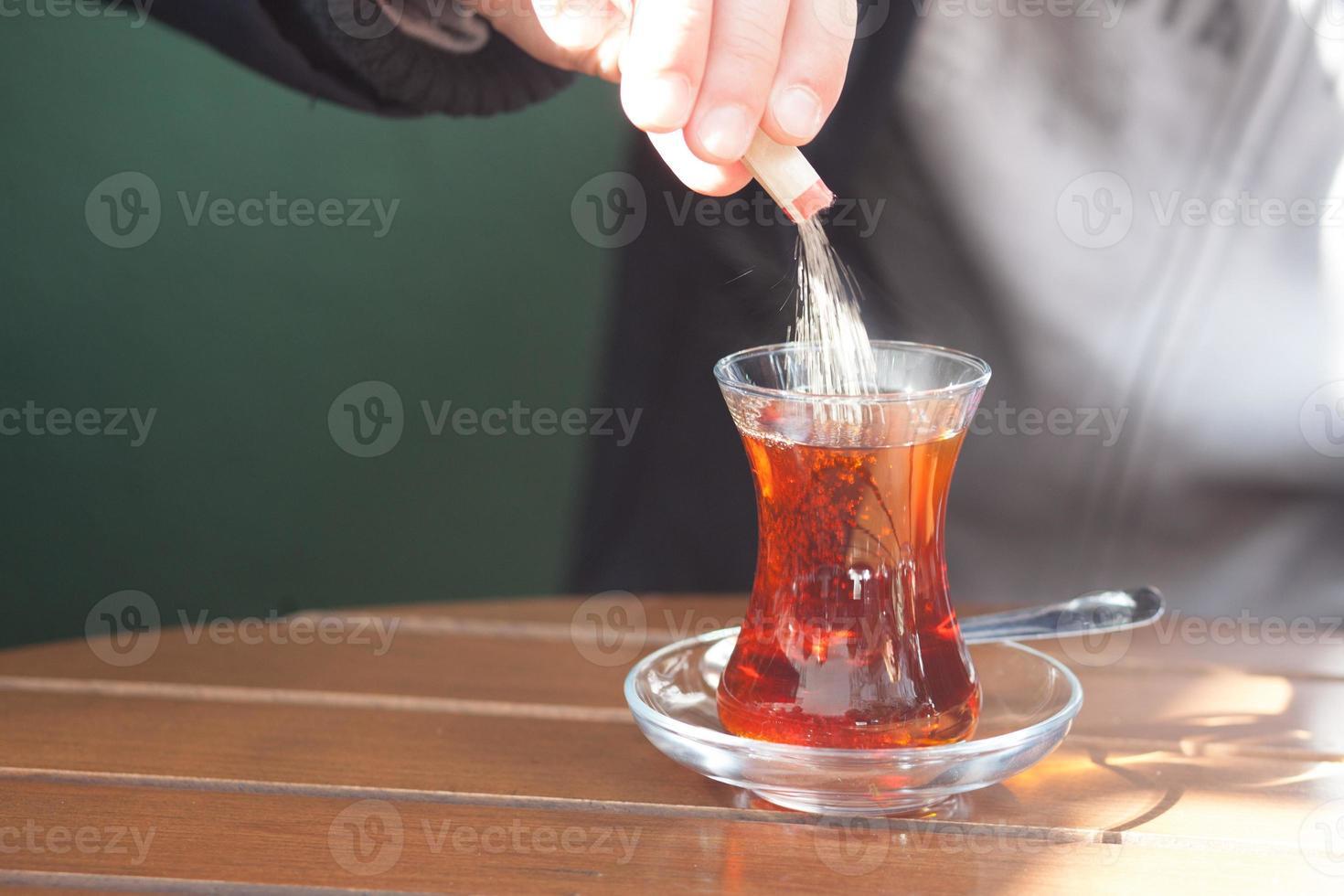 Person, die Zucker in Tee gießt foto