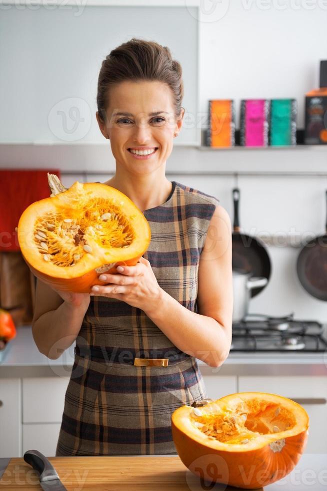 glückliche junge Hausfrau zeigt die Hälfte des Kürbises foto