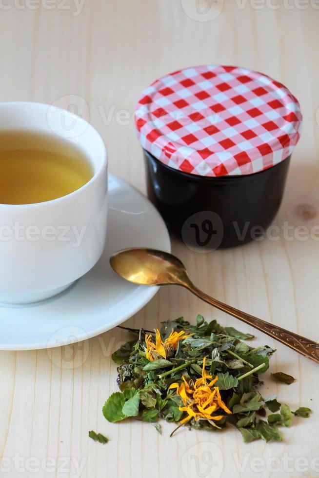 Tasse Kräutertee und Marmeladentopf foto