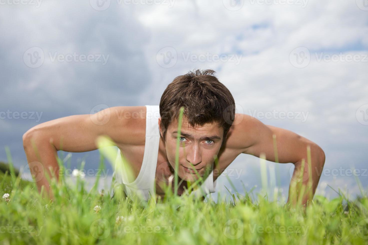 junger Mann, der im Park trainiert foto