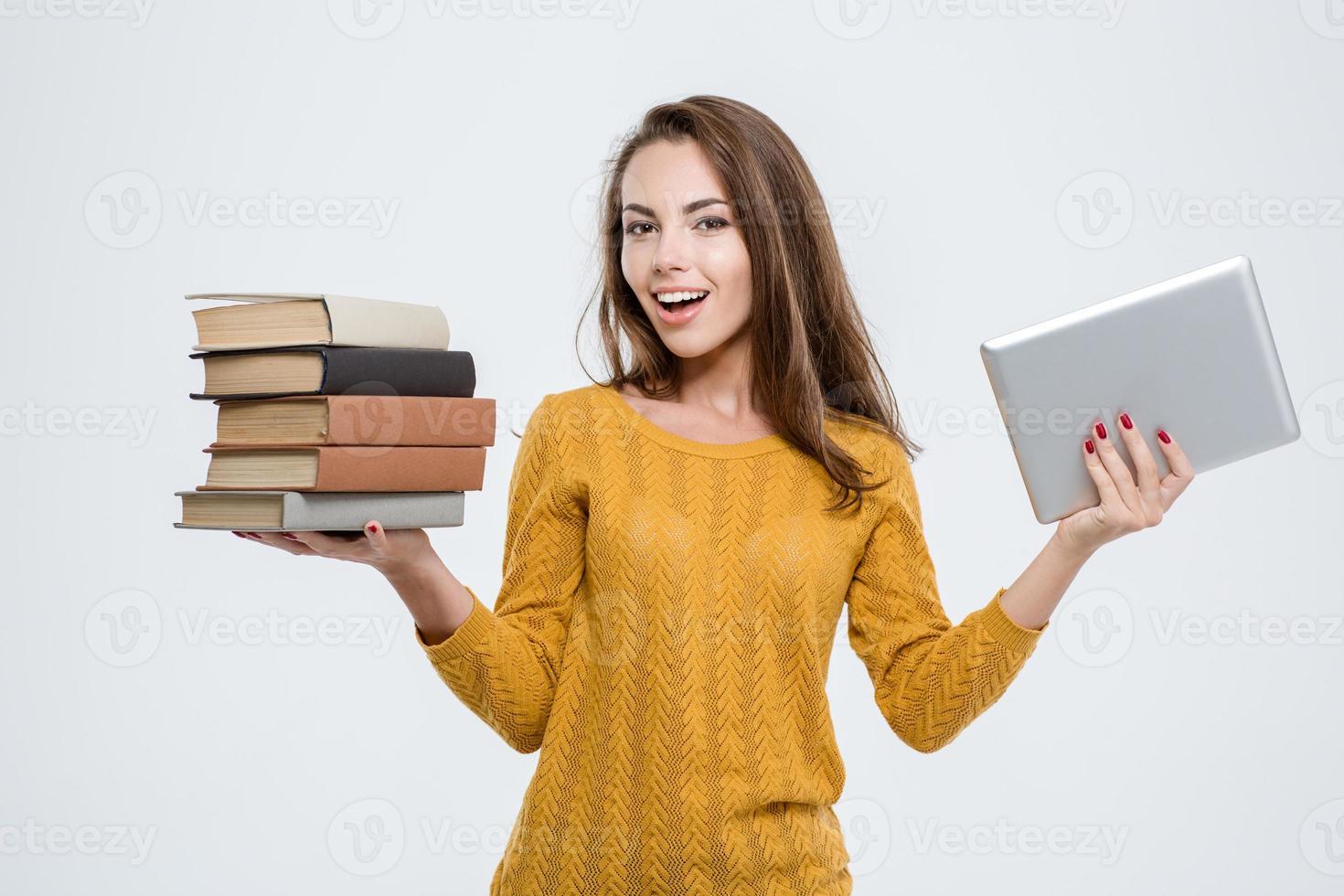 Frau, die zwischen Papierbüchern oder Tablet-Computer wählt foto