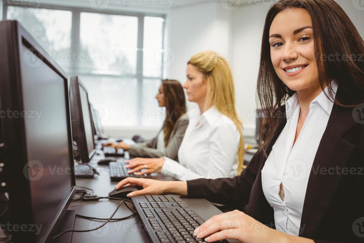 glückliche Frau im Computerraum, die Kamera lächelt foto