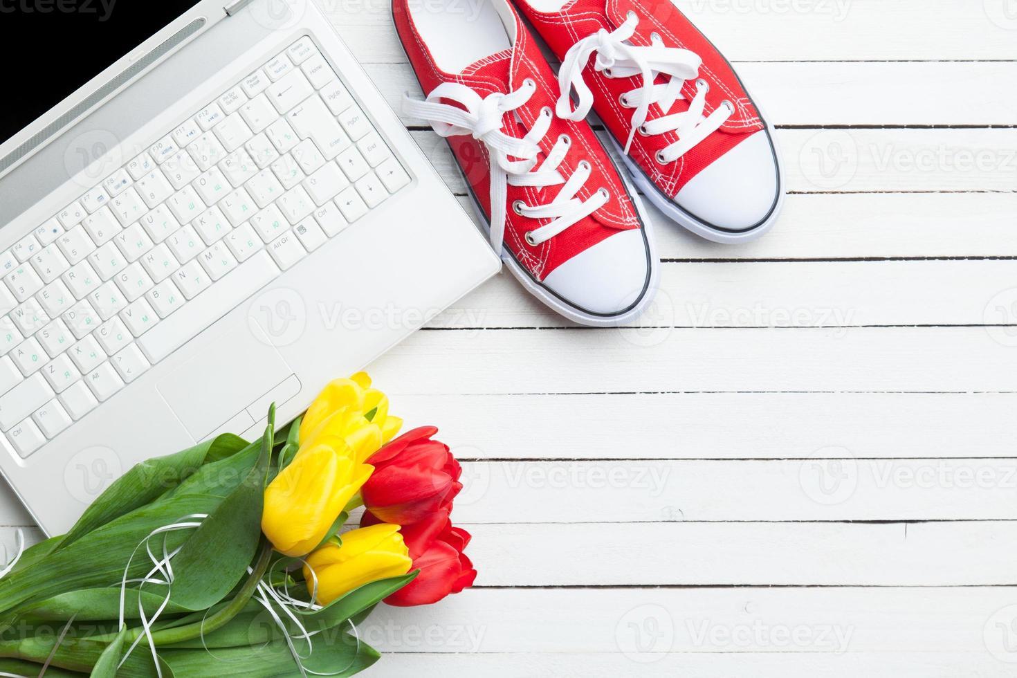 weißer Computer und Tulpenstrauß mit Gummischuhen foto