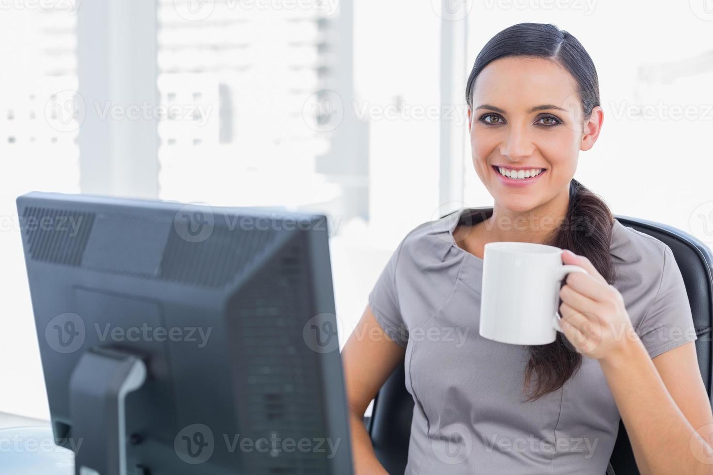 lächelnde attraktive Geschäftsfrau, die Becher hält foto