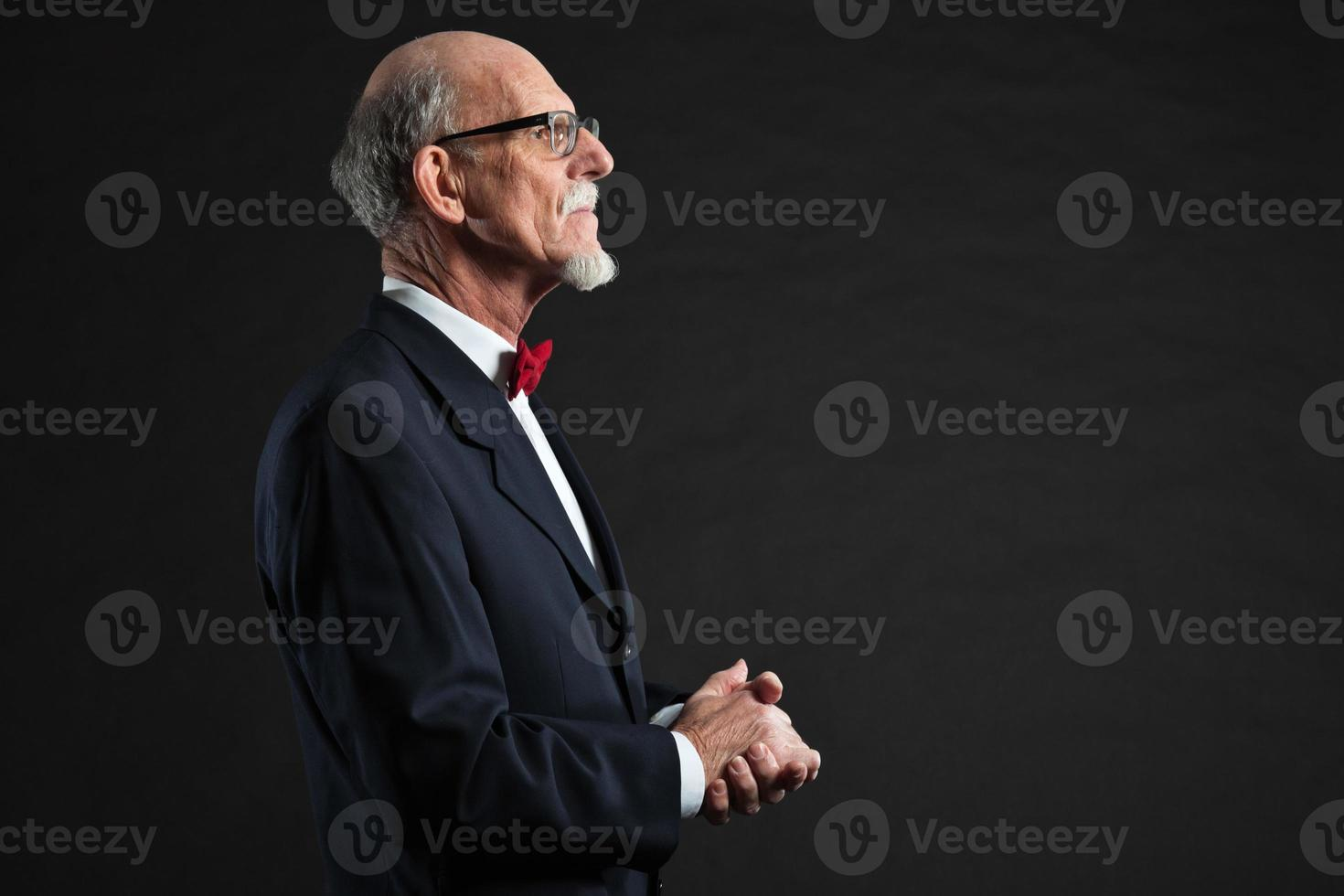 älterer Mann, der Anzug und rote Krawatte trägt. Studioaufnahme. foto