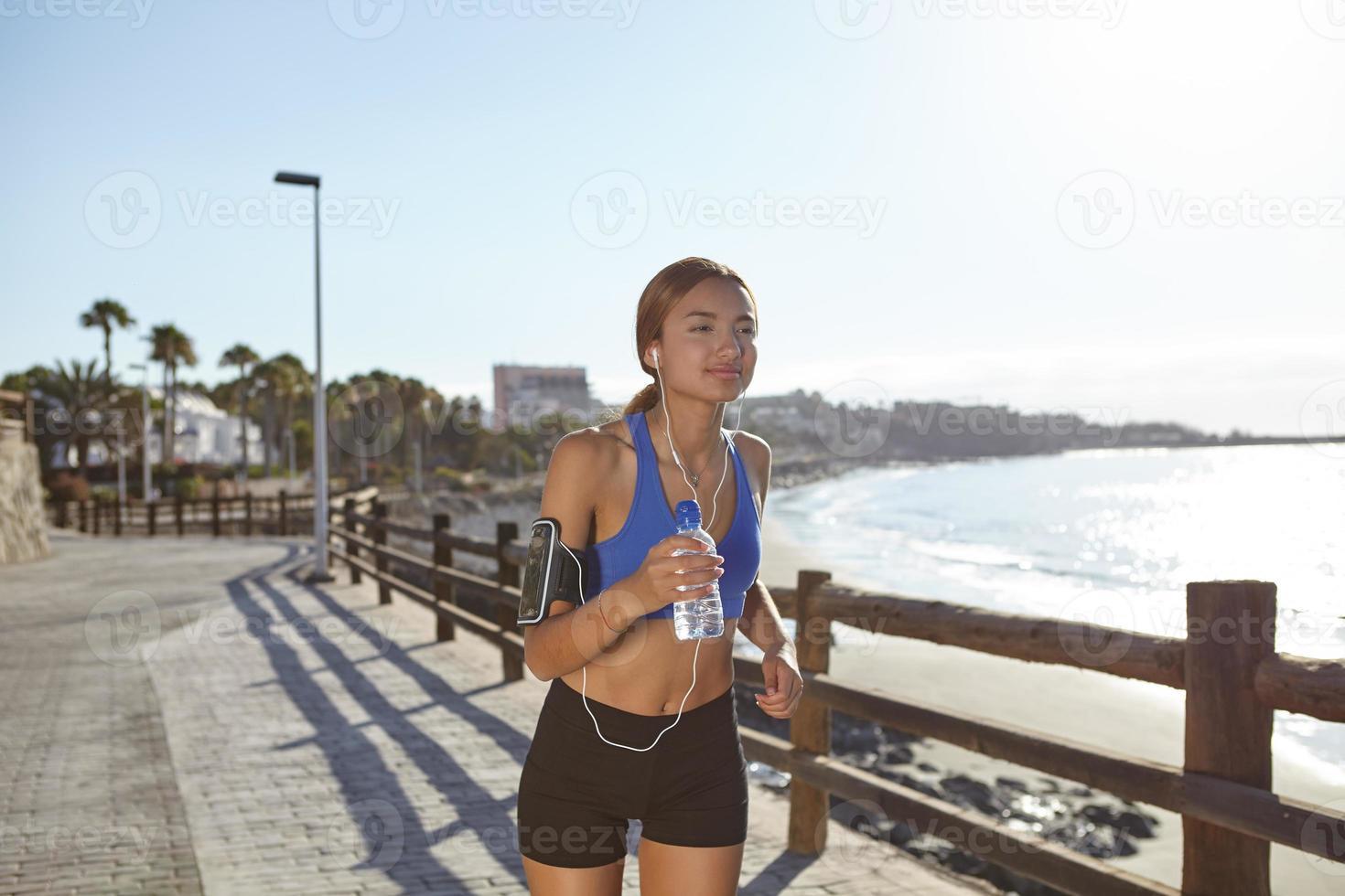 junger Athlet, der am Strandufer läuft foto