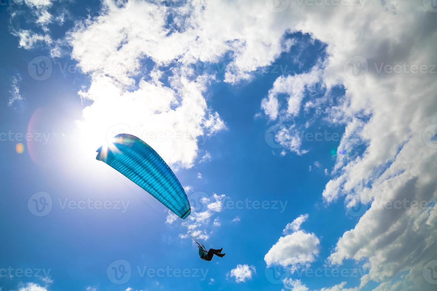 Gleitschirm schwebt in einem sonnigen blauen Himmel foto