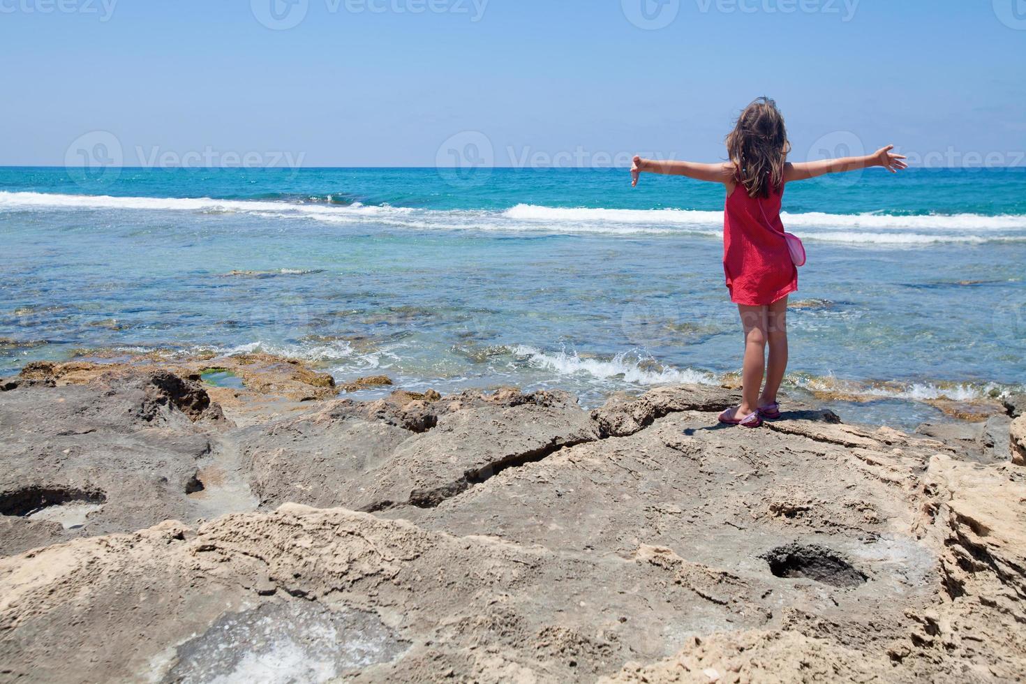 kleines Mädchen, das in einem Wind vom Meer genießt foto