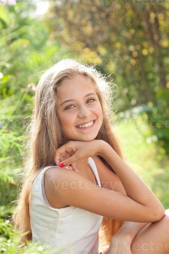 Porträt des hübschen Mädchens, das sitzt, lächelt und die Natur genießt foto
