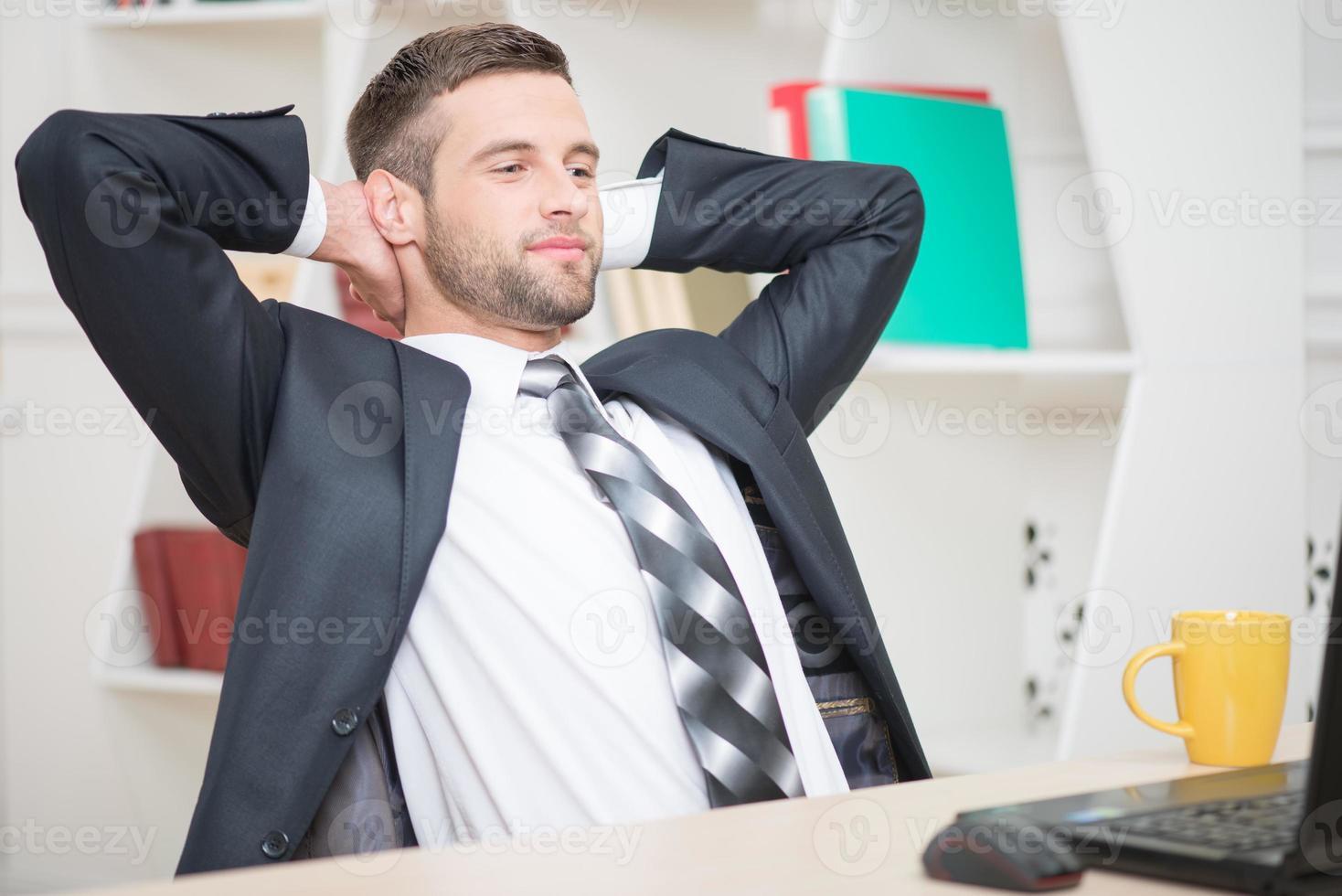Porträt des gutaussehenden Geschäftsmannes, der die Kaffeepause sitti genießt foto
