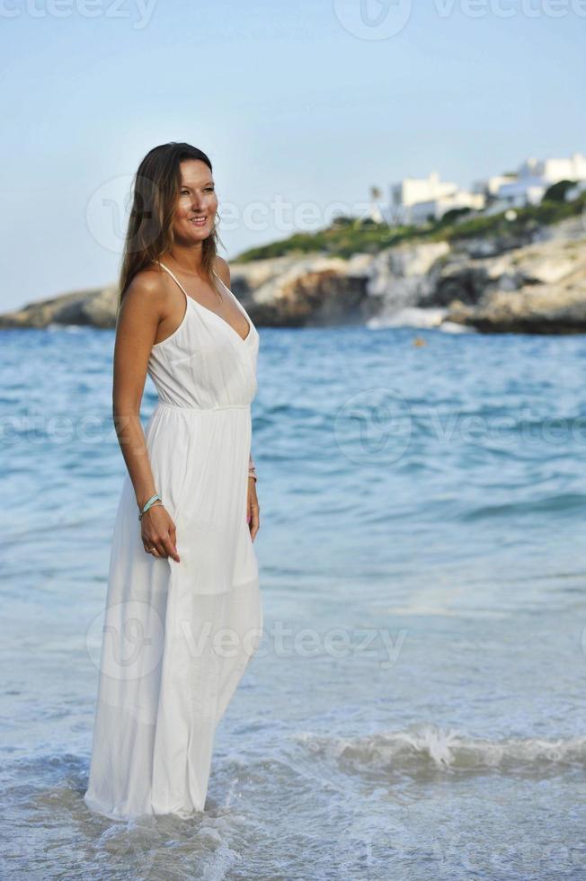 schöne Frau genießt Urlaubssommerferien am Strand spazieren foto