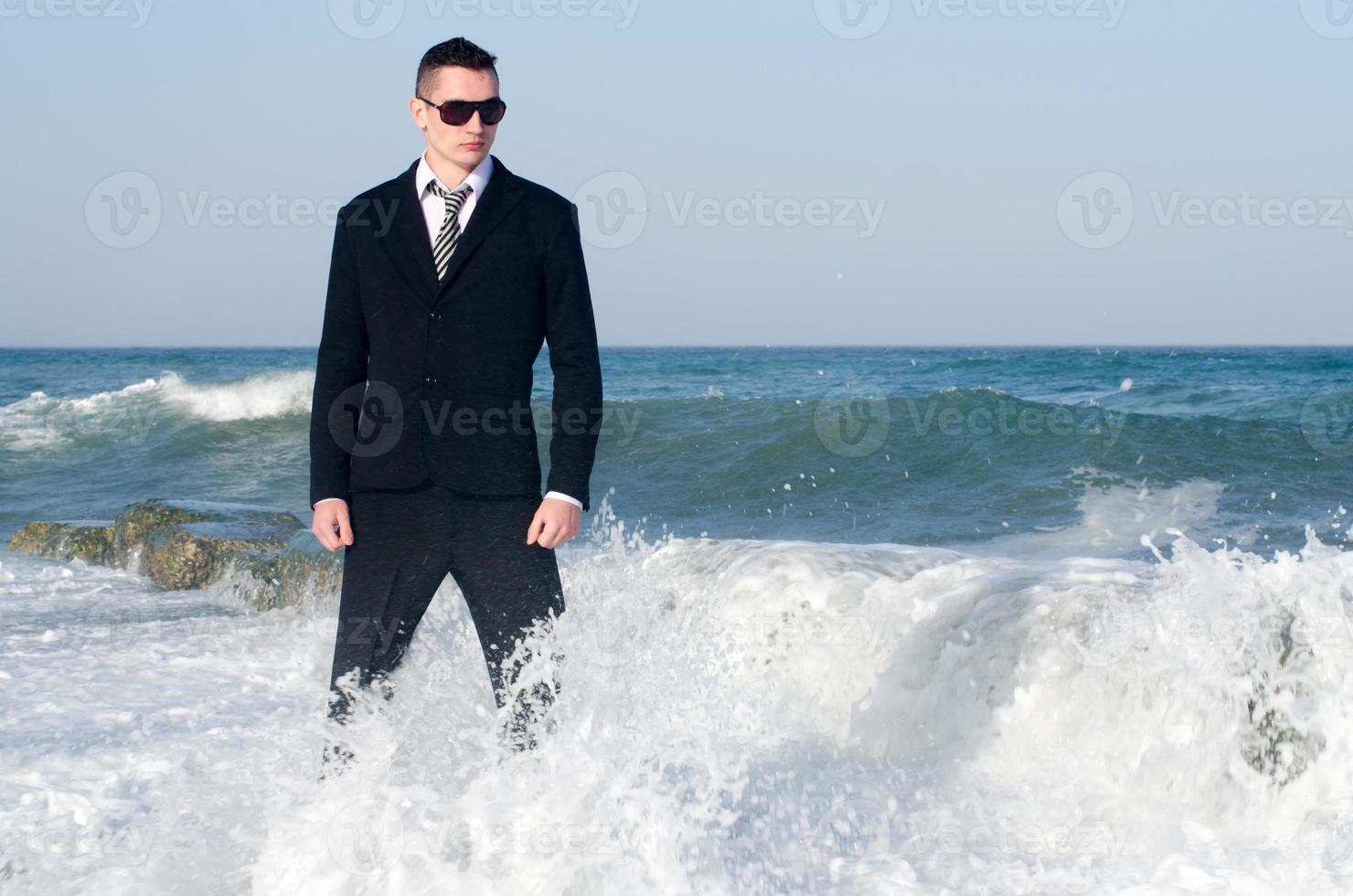 junger schöner Geschäftsmann, der seine Zeit am Strand genießt foto
