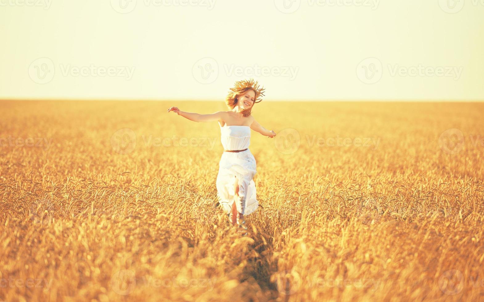 glückliche junge Frau, die das Leben im goldenen Weizenfeld genießt foto