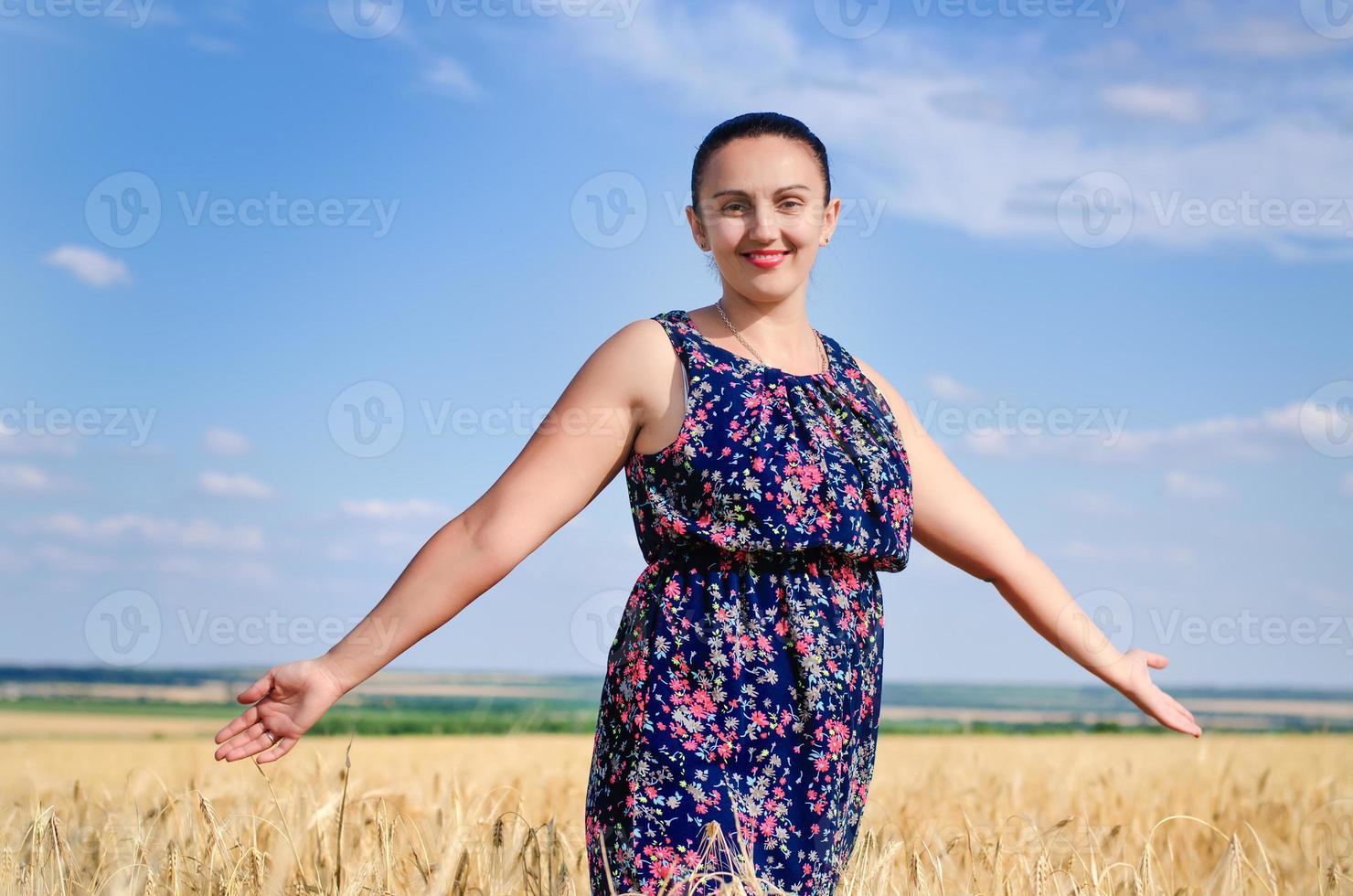Frau stehend, die die Sonne in einem Weizenfeld genießend foto