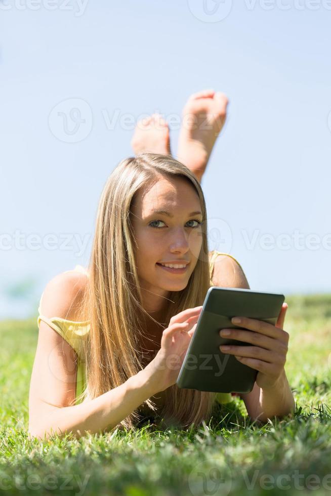 Mädchen, das auf Gras in der Wiese liegt und Ereader liest foto