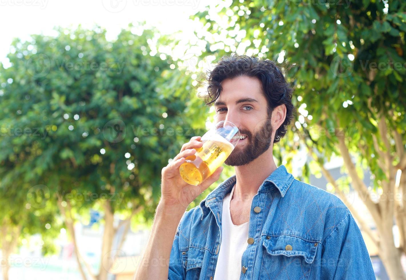 Mann, der ein Biergetränk an der Außenbar genießt foto