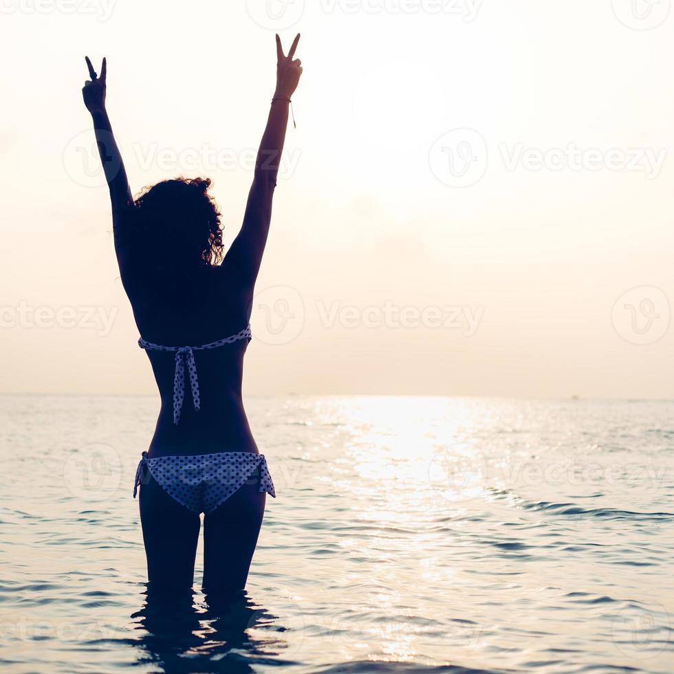 Frau, die die Freiheit genießt, sich am Strand bei Sonnenuntergang glücklich zu fühlen foto