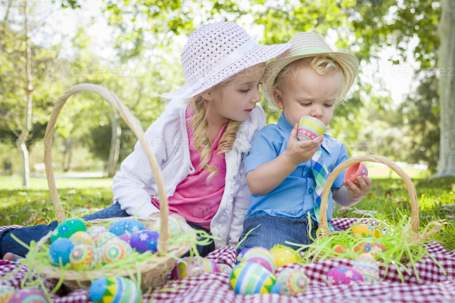 süßer junger Bruder und Schwester genießen ihre Ostereier draußen foto